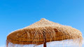 Wooden straw sun umbrella background with clear blue sky Stock Image