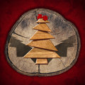 Wooden and stylized christmas tree red comet on on section of trunk red velvet background Royalty Free Stock Images