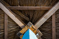 Wooden sunshade straw umbrella with a blue foot view from below Royalty Free Stock Photo