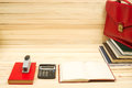 On a wooden table books, documents, calculator, red briefcase. Royalty Free Stock Photo