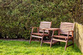 Wooden table and chairs on a green lawn in the backyard on a sunny day background hedgerow old fence Stock Photos