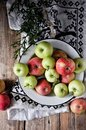 On a wooden table on a cotton towel a metal dish with fresh red and green apples Royalty Free Stock Photo
