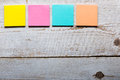 Wooden table with empty colorful sticky notes Royalty Free Stock Photo