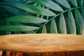 wooden table in front of tropical green floral background. for product display and presentation Royalty Free Stock Photo