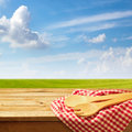 Wooden table with kitchen utensil over green meadow and blue sky Royalty Free Stock Photo