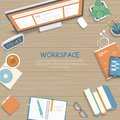 Wooden table with monitor, books, notebook, headphones, pencils. Workplace background top view.