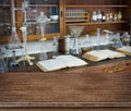Wooden table over defocused vintage chemical laboratory background Royalty Free Stock Photo