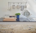 Wooden table top with blur of modern ceramic kitchenware and utensils Royalty Free Stock Photo