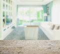 Wooden table top with blur of modern style living room interior Royalty Free Stock Photo