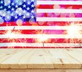 Wooden table on USA flag with sparklers background