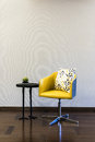 Wooden table yellow chair combination in front of a plain wall Royalty Free Stock Photo