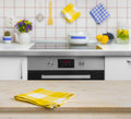 Wooden table with yellow napkin on kitchen background Royalty Free Stock Photo