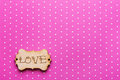 Wooden tag with word Love on pink