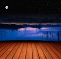 Wooden terrace with lake landscape full moon and a starry sky Royalty Free Stock Image