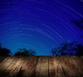 Wooden terrace with star trails background Royalty Free Stock Image
