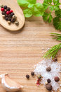 Wooden texture background with cooking ingredients sea salt crystals peppers garlic fresh herbs basil dill and parsley Stock Photos