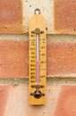 Wooden thermometer hanging outside on a brick wall Stock Images