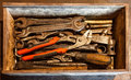 The wooden tool box of hand tools with old and dirty, rusty wrenches, ring spanners, pliers, screwdrivers, chisel and other do-it- Royalty Free Stock Photo