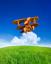 Wooden toy airplane flying in summer blue sky vacations concept Stock Photos