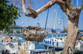 Wooden toy boat hanged from a tree in the harbor of poros island greece Royalty Free Stock Image