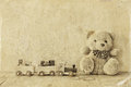 Wooden toy train and teddy bear over wooden floor. black and white style photo