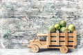 Wooden toy truck with a green Christmas balls in the back on a g Royalty Free Stock Photo