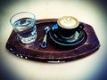 A wooden tray with a cup of cappuccino with plate and teaspoon as well as a glass of sparkling water image stylized with cross Stock Photography