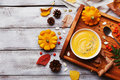 Wooden tray with hot autumn pumpkin soup decorated sesame seeds and thyme in white bowl on rustic vintage table top view. Royalty Free Stock Photo