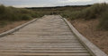 Wooden walkway a leading into the distance with hand rails in sand dunes Stock Image