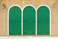 Wooden wall and painting with three green doors pattern Royalty Free Stock Photo