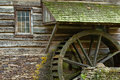 Wooden water paddle wheel and mossy stones on the side of a old Royalty Free Stock Photo