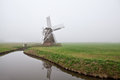 Wooden windmill in fog Royalty Free Stock Photo