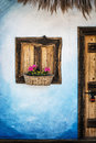 Wooden window with flowers, blue wall and door with padlock, retro style Royalty Free Stock Photo