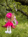 Woodland fairy doll pink girl sitting on a swing in a garden Royalty Free Stock Images