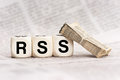 Woodn dice spelling rss depicting the letters with a stack of newspapers leaning on a Royalty Free Stock Photo