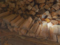 A woodpile of fire wood in a shed ray light on Royalty Free Stock Photos