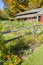 Woodshed and garden with split rail fence colorful autumn scenic of a country flower a in the foreground a metal roof in the Stock Photos