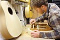 Woodworker building guitar in workshop a young man who is a luthier is making hand made out of wood his home Stock Photography