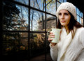 Wool dressed girl with mug against glass wall Stock Photography