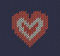Wool knitted pattern with red heart on blue background.