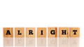 The word alright on wooden blocks cubes arranged in a line a reflective white surface with copyspace above Stock Photos