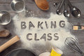 Word baking class written in white flour on a old wooden table from top view vintage tone surrounding by tools Stock Photos