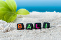 Word Bali is made of multicolored letters on snow-white sand against the blue sea. Royalty Free Stock Photo