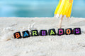 Word Barbados is made of multicolored letters on snow-white sand against the blue sea. Royalty Free Stock Photo