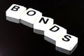 The word bonds a term used for business in finance and stock market trading spelled out with white tiles on black background Stock Photos