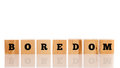 The word boredom on wooden cubes arranged in a line a reflective white surface with copyspace above Royalty Free Stock Photography
