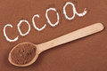 Word cocoa written in cocoa powder with a wooden spoon Royalty Free Stock Photo