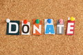 The word donate in cut out magazine letters pinned to a cork notice board Stock Photography