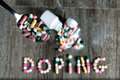 The word doping written with pills on a wooden background Royalty Free Stock Image