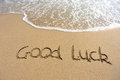 Word good luck drawn on the beach and sea wate Stock Image